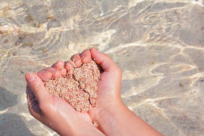 Serduszko wdłoniach zróżowego piasku nalagunie Balos.