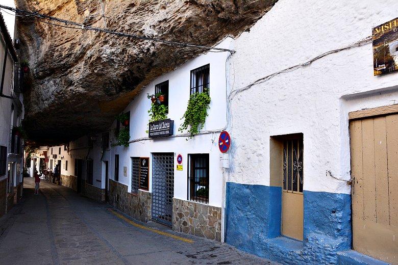 Wybrukowana uliczka zbiałymi budynkami umieszczonymi podogromnym skalnym nawisem.