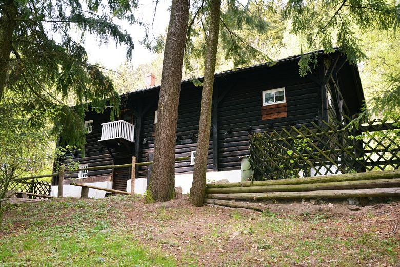Czarny drewniany domek przy schronisku Szwajcarka.