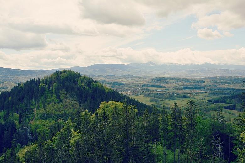 Krajobraz zSokolika Dużego naKrzyżną Górę irozciągające się wtle Karkonosze.